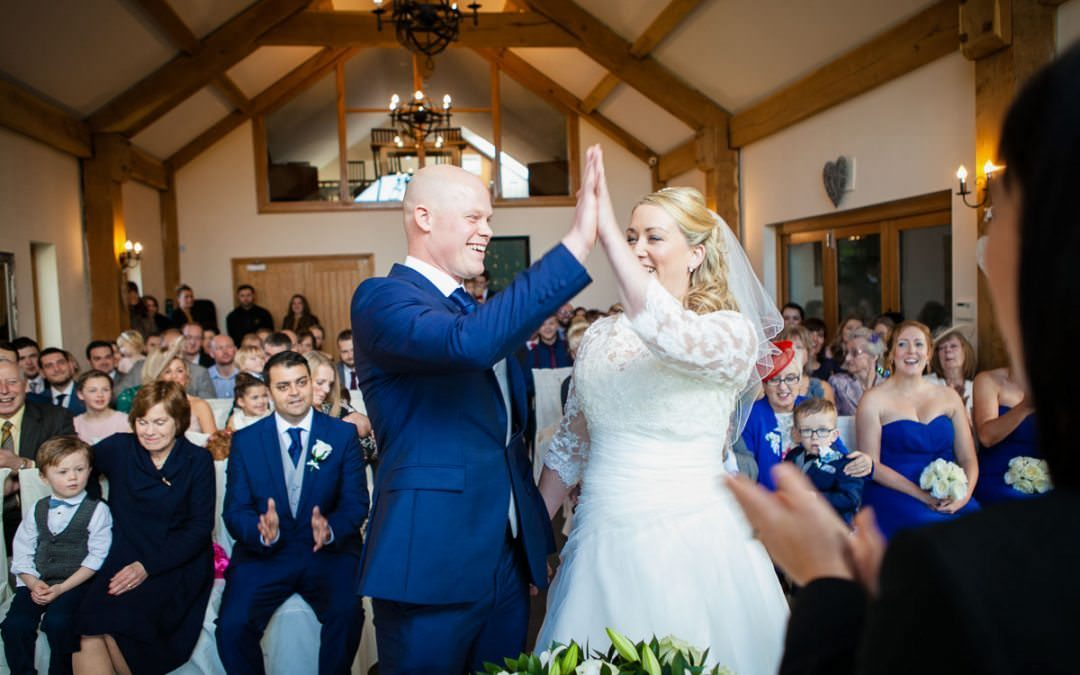Newly married couple high five each other after ceremony