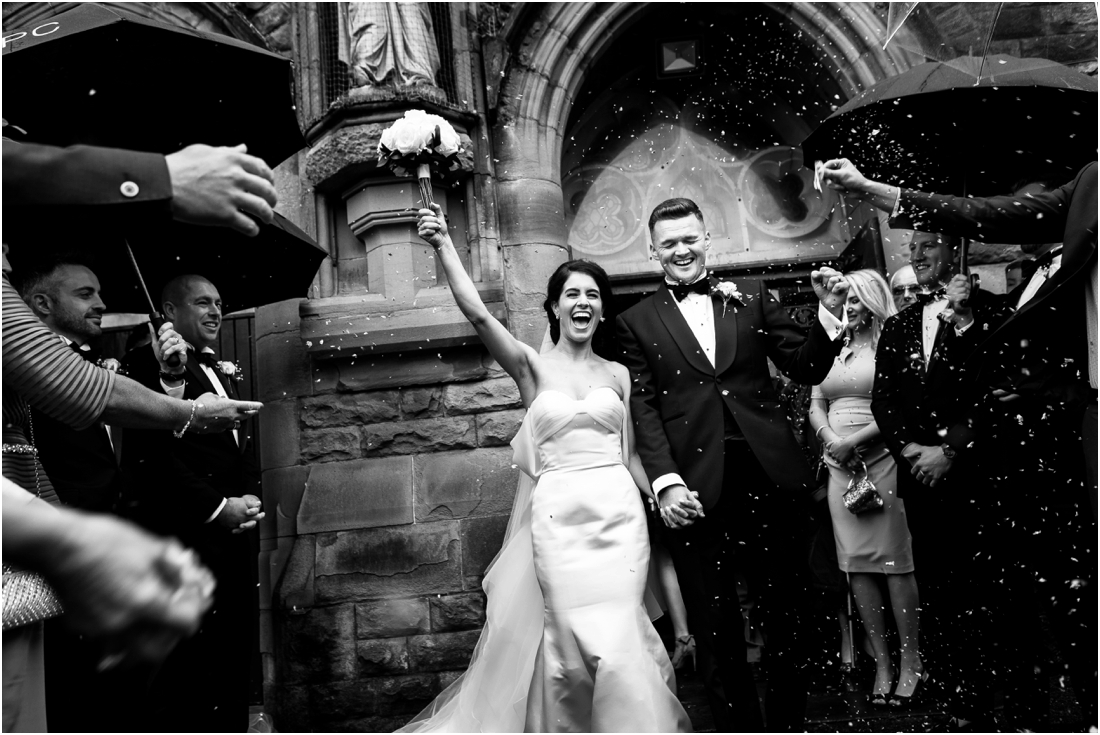 black and white bride and groom leaving church cheering