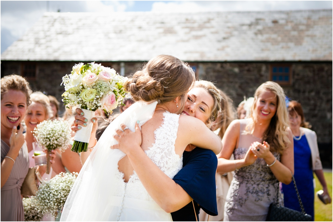 wedding guest hugs bride after catching bouquet
