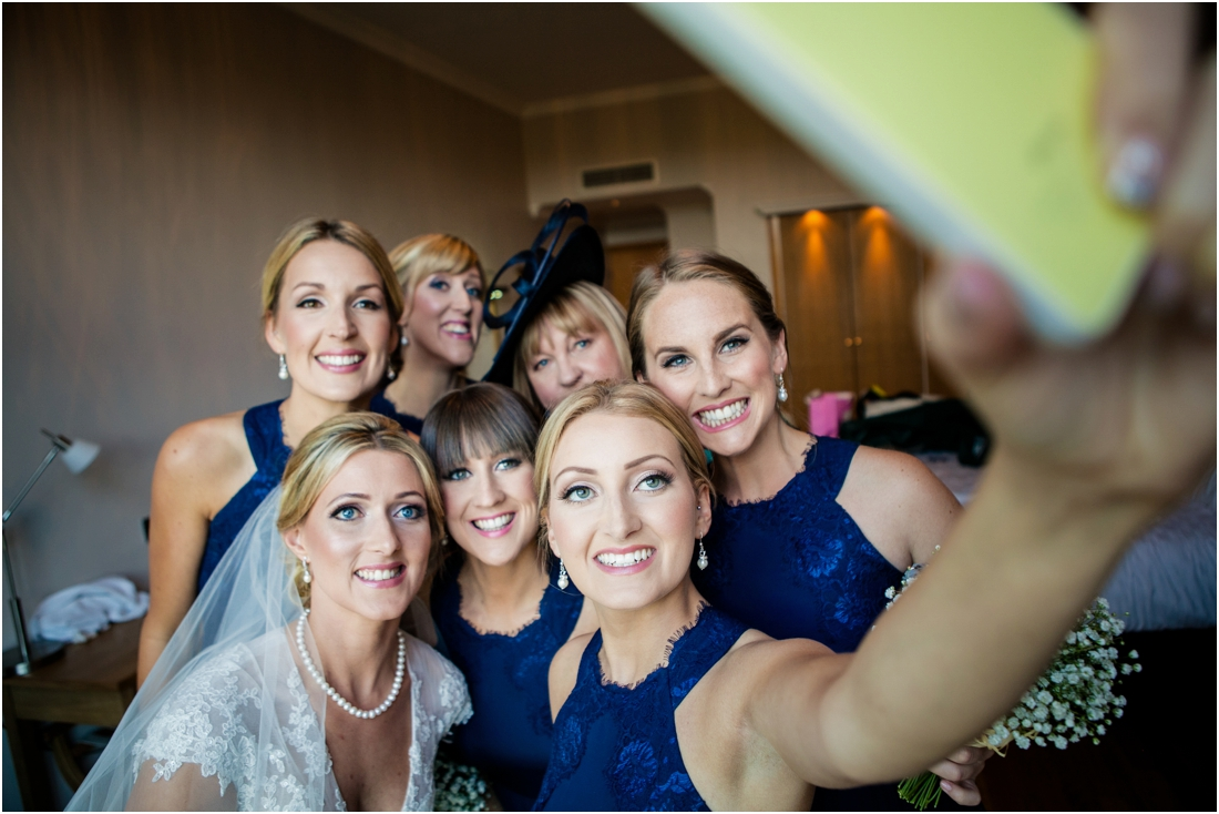 bride and bridesmaids having a selfie before wedding ceremony