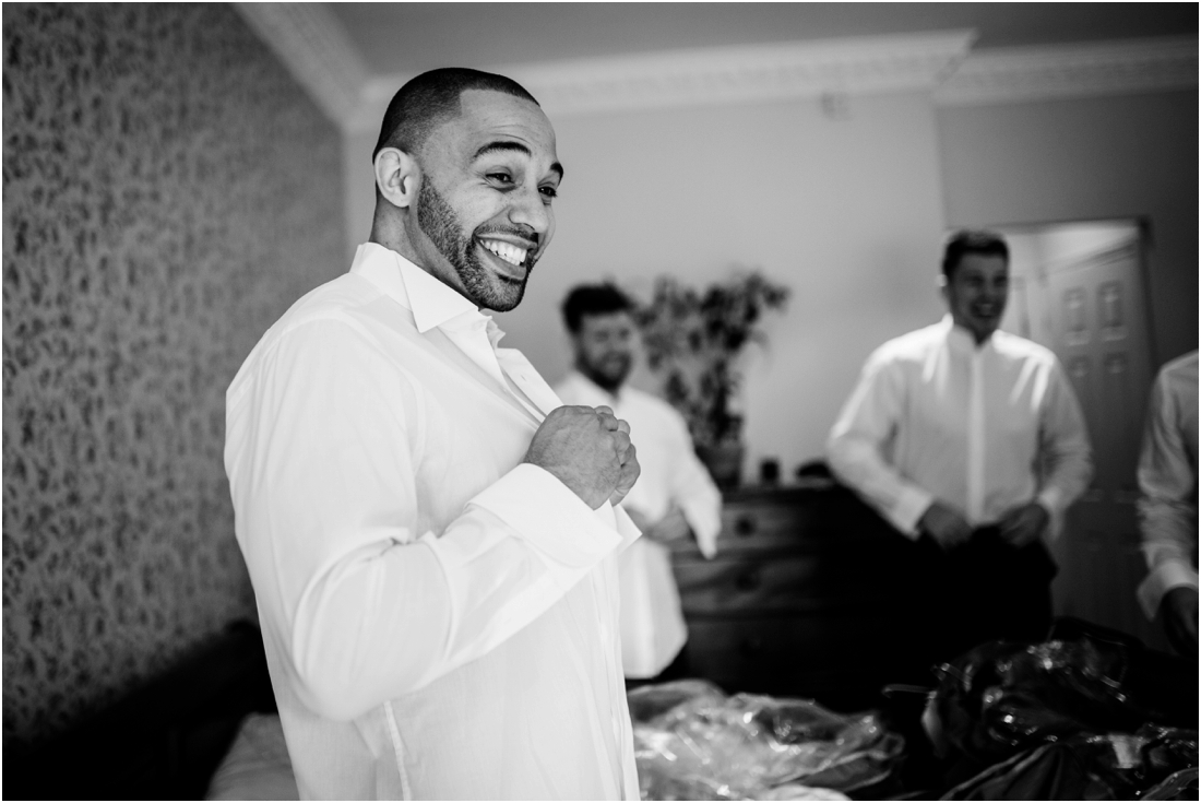 groom laughing getting ready