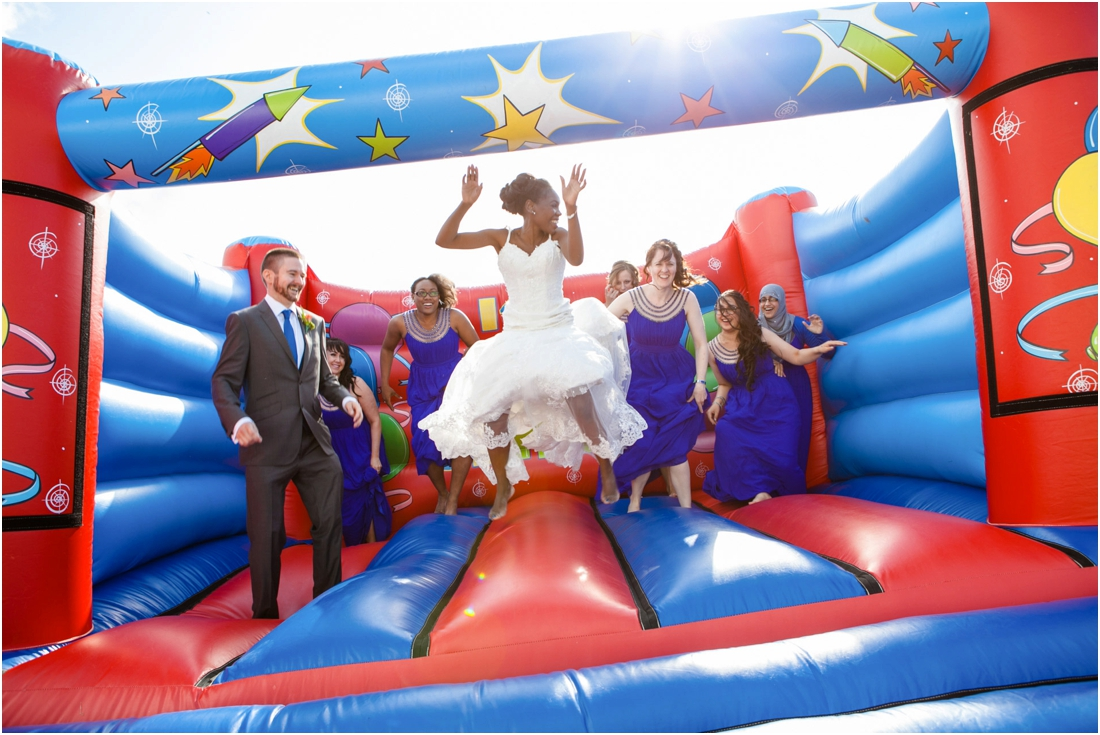 wedding party jumping on bouncy castle
