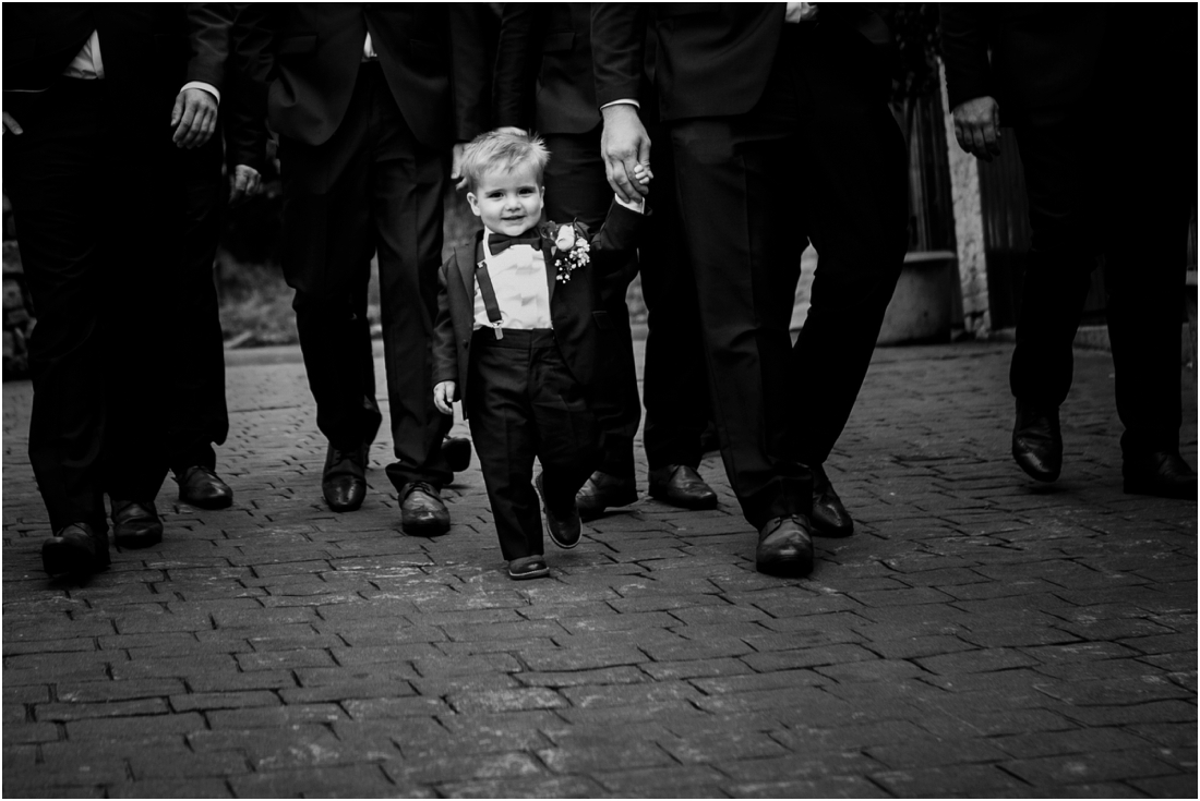 black and white image of little boy with groomsmen