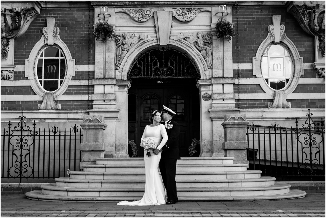 black and white image of bride and groom outside morgans hotel swansea