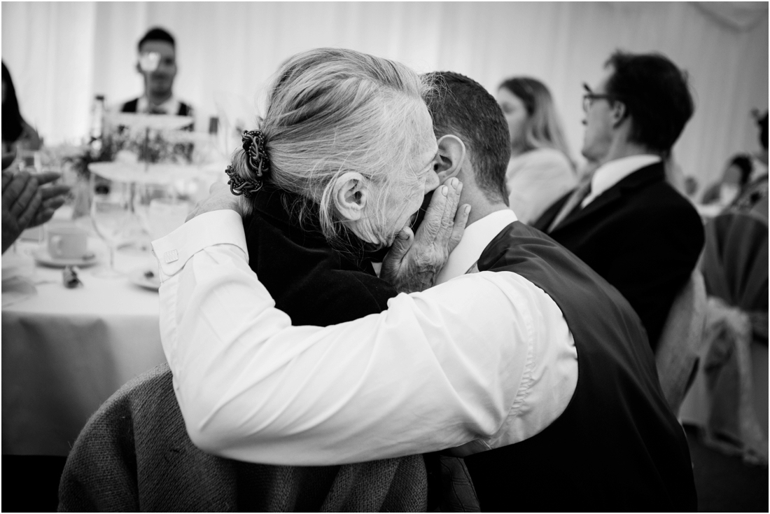 groom hugging crying grandmother